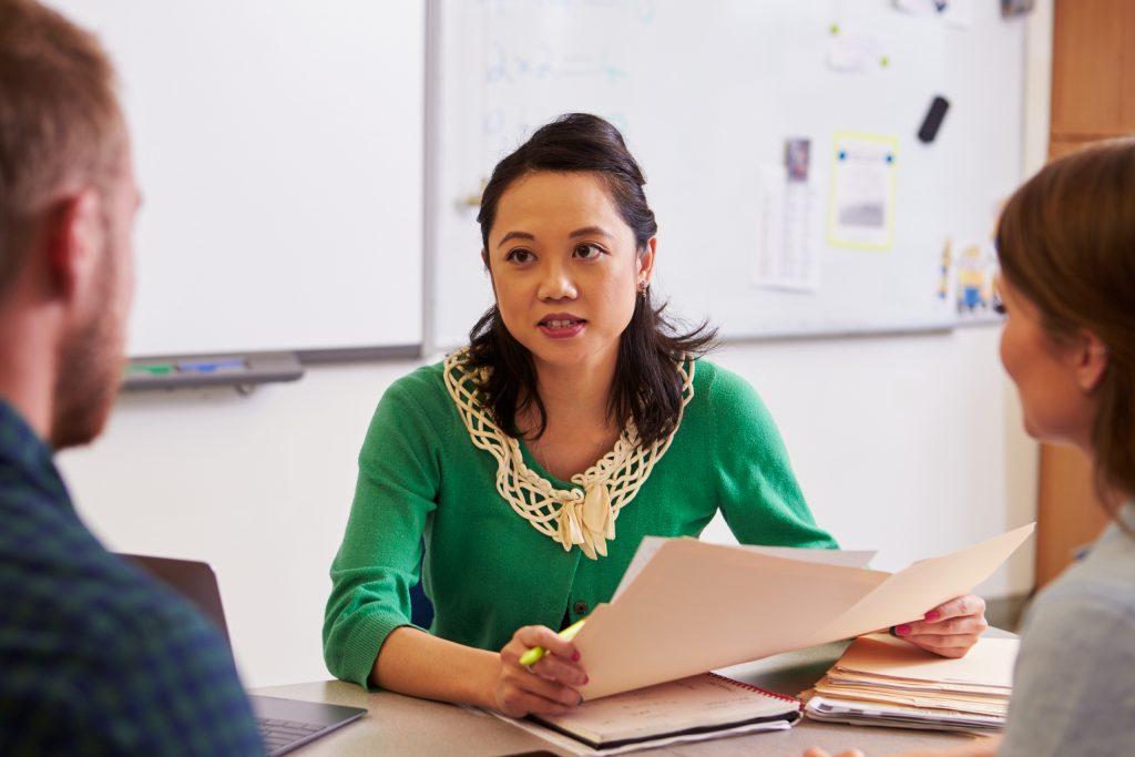 Teacher at desk talking with parents